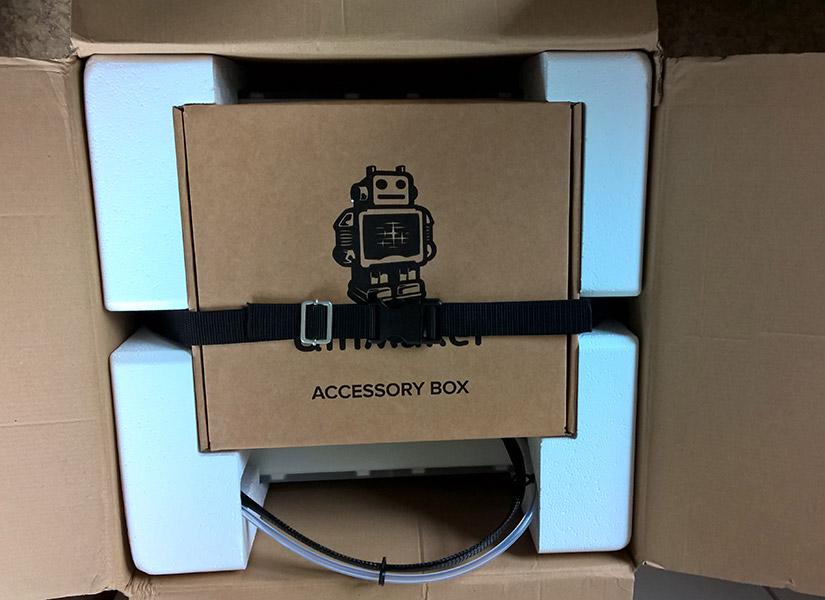 Unboxing made easy - nettes Detail am Rande, mit diesem Gurt kriegt man den Drucker problemlos aus der Schachtel